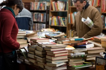 Image of books piled up on a table with multiple bookshelves in the background showing a bookstore for shopping in NJ