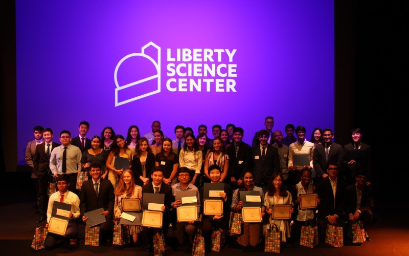Image of children holding up diplomas under a liberty science center sign
