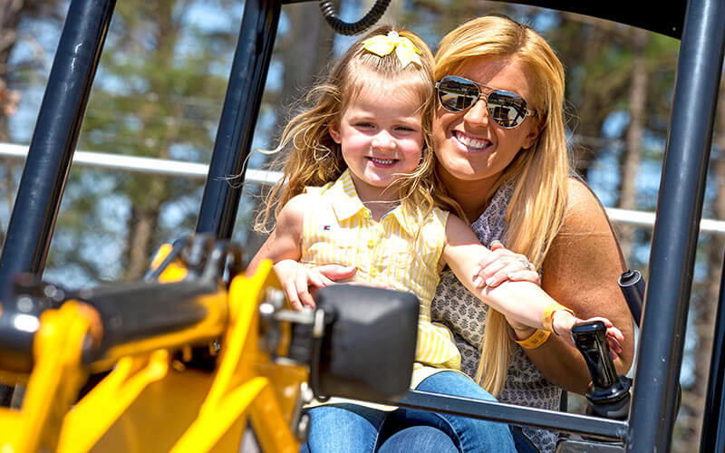 Mom and daughter dig with a real excavator at Diggerland USA in West Berlin, NJ