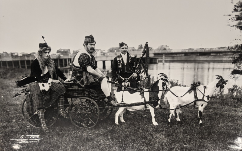 Image of Scottish men riding a carriage with goats pulling it