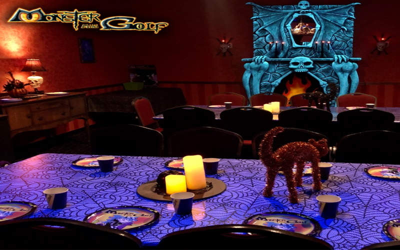 Image of monster mini golfs party room with a decorative cat and candles on the table