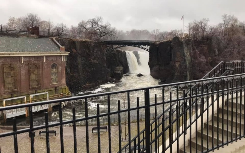 Image of a waterfall and a red brick house.