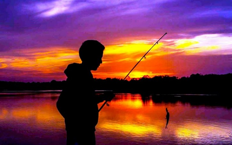 Image of a silhouette of a boy fishing with a sunset behind.