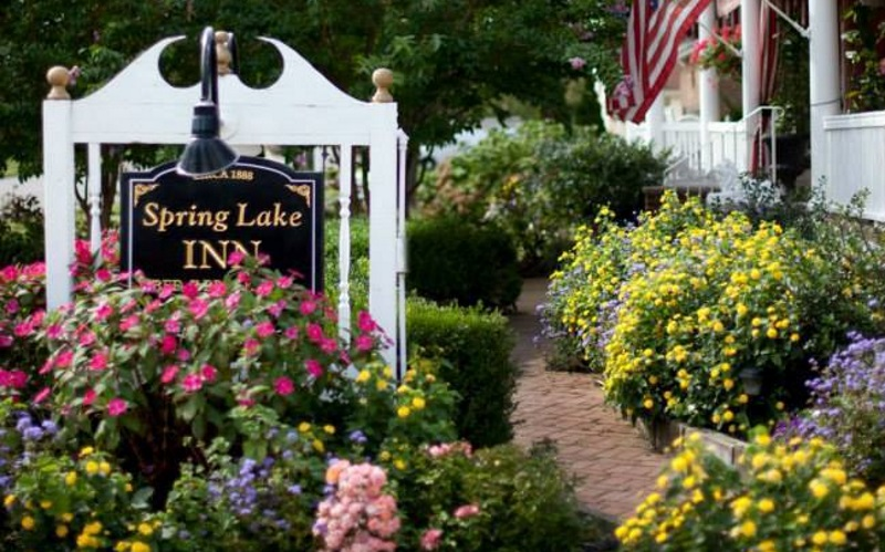 A image of the front of the spring lake inn with flowers and a sign
