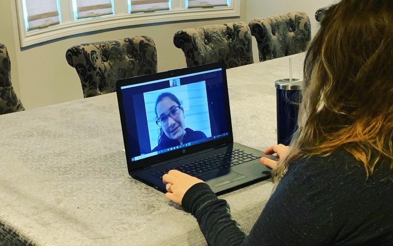 Image of a girl and a woman video conferencing on a black laptop on a kitchen table.
