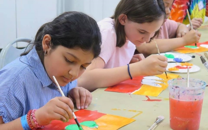 Image of children painting with acrylic paints.